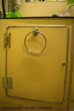 Lo siguiente es agregarle dos bisagras a esta puerta. Estas las vamos a unir al lateral izquierdo del marco de la puerta del mueble cosa que la puerta abra hacia la pared del baño. Con esto ya tenemos colocada la puerta del mueble.